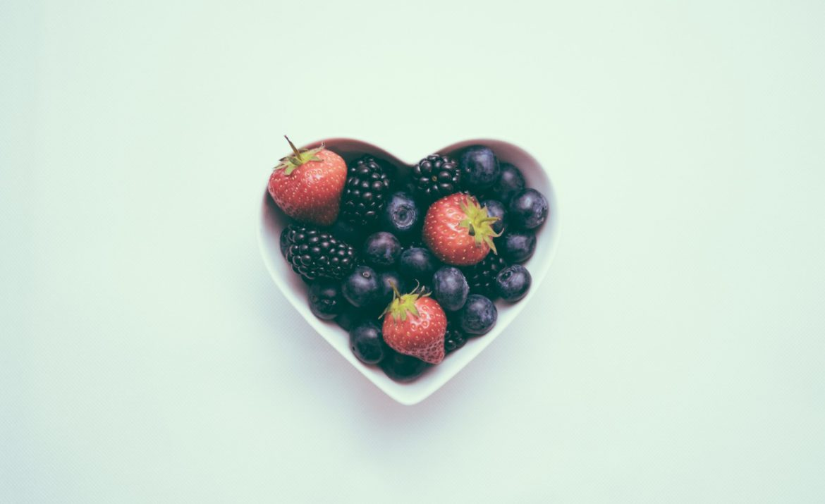 bowl shaped like a heart, filled with blueberries and strawberries